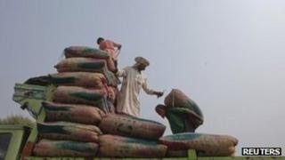 Men load sacks of dates onto a truck at a dry port before transporting them to India at Wagah border, on the outskirts of Lahore November 3, 2011.