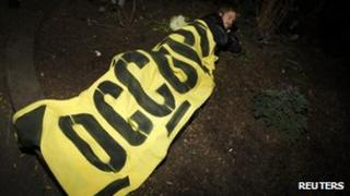 A protester lies down under an Occupy banner in Zuccotti Park 15 November 2011