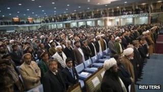 Members of the loya jirga stand up as the national anthem plays in Kabul November 16, 2011