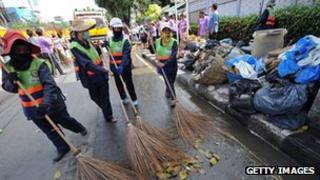 Bangkok workers cleaning up a major street.