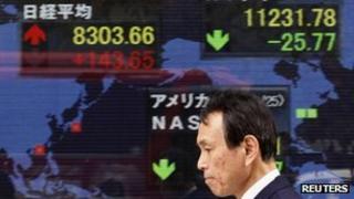 Man walks past an electronic markets board