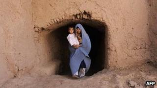 Afghan woman holds her baby as she walks in the outskirts of Herat in October 2011