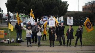 PCS (Public and Commercial Services) union members wave flags at cars near Heathrow Airport
