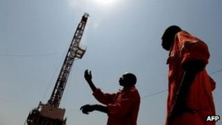 Two workers born in the oil reach Southern Sudan state of Unity, stand on the drilling site number 102 in the Unity oil field in Southern Sudan on November 11, 2010.