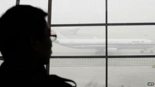 A traveller looks out at an airplane shrouded in smog at Beijing International Airport