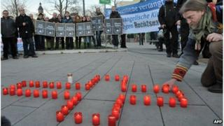 A man lights candles during a commemoration vigil for the victims of a murder series allegedly committed by a right-wing terror group, on November 28, 2011 in Erfurt, eastern Germany