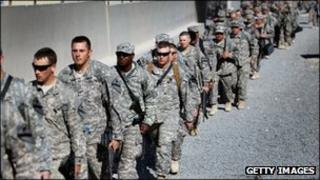 Army soldiers from the 1st Cavalry Division walk to a waiting bus as they leave customs for a ride to the airport to fly back to Fort Hood from Kuwait after exiting from Iraq