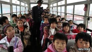 A primary school security personnel checks the number of pupils on a school bus in Zouping county, China's Shandong province, 17 November 2011