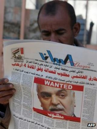 """An Iraqi man in Baghdad reads a local newspaper, featuring a front page picture of Vice-President Tareq al-Hashemi with the word """"wanted"""" above his face, on December 20, 2011."""
