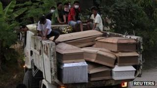 Coffins containing typhoon victims are carried on a truck in Iligan city, southern Philippines (20 Dec 2011)