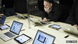Shopper looks at Apple's laptops