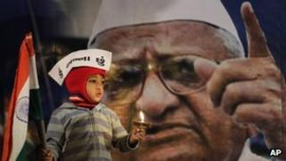 "A young supporter of Indian anti-corruption activist Anna Hazare, depicted in photograph in background, wears a cap that reads ""I am Anna"" as he hold the Indian flag during a protest against corruption in Ahmadabad, India"
