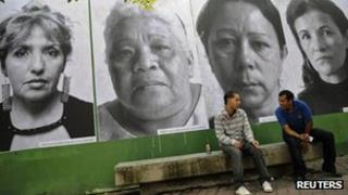 Men sit in front of giant portraits of mothers whose children have been victims of violence in Caracas