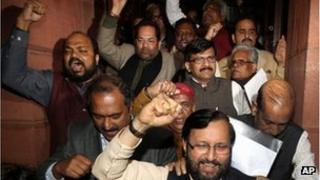 Indian Law makers from opposition parties shout slogans against ruling Congress party as they come out of parliament house after a debate on anti corruption bill in the Upper house, in New Delhi, India, Friday, Dec. 30, 2011