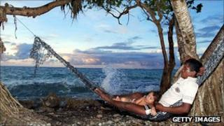 Man and his daughter relax in a hammock on the sea edge