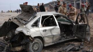 Iraqi security forces inspect the scene of a car bomb attack outside the northern city of Mosul