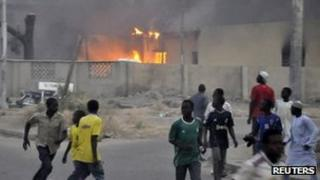People run for safety as a police office burns in Kano. Photo: 20 January 2012