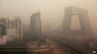 Heavy pollution surrounds the China Central Television (CCTV) headquarters building (R) in Beijing on January 18, 2012