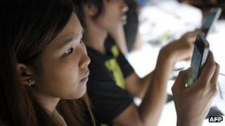 Customer looks at smartphone in Bangkok, Thailand
