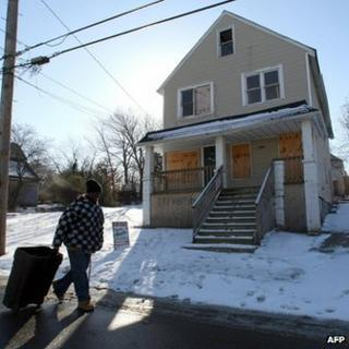 A man walks past a boarded up building in the Mount Pleasant section of Cleveland, Ohio, in January 2008