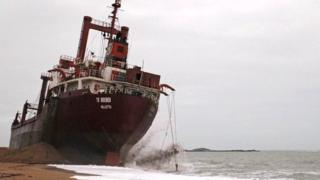 Workers are seen in front of the Maltese-registered cargo ship the TK Bremen, on Kerminihy beach at Erdeven