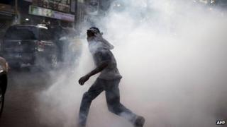 "An anti-government protestor flees from tear gas at a protest in Senegal""s capital Dakar, February 21, 2012"