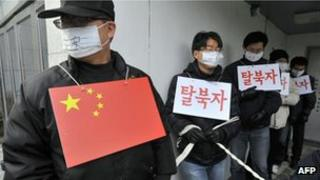 South Korean rights activists perform role of mock Chinese police and North Korean refugee outside the Chinese embassy in Seoul on 21 February, 2012