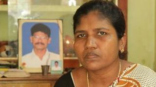 Dora, widow of fisherman Valentine (in picture in background). Kerala state, India