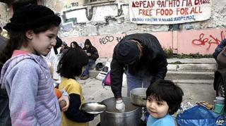 People receive food from a humanitarian group at a housing complex in the centre of Athens