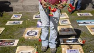 Human rights activists place flowers next to the portraits of people who disappeared during the armed conflict in Guatemala, on 24 February 2012 in Guatemala City
