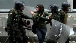 A protester is detained by riot police in Bogota