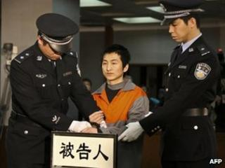 Shi Baikui (C) arrives under police escort for his sentencing at the Second Intermediate People's Court of Beijing, 19 March 2012