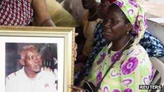 Relatives of slain Guinea Bissau ex-military intelligence chief Samba Djalo mourn his death next to a portrait of him in the capital Bissau, March 19, 2012.