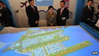 Eva Cheng, Secretary for Transport being shown a map of the International Airport with the proposed third runway