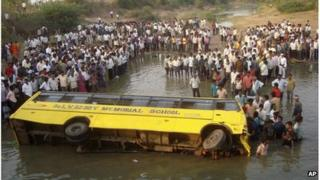 Indians gather near a school bus that fell into a pond near Tungaram village in Khammam district, about 250 kilometers west of state capital Hyderabad, India, Tuesday, March 20, 2012