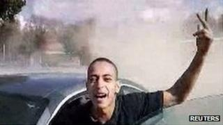 Image of Mohamed Merah next to a car, waving his hand in the air
