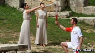 High Priestess Maria Nafpliotou lights the torch of first torchbearer Alexandros Nikolaidi in the Ancient Stadium during the Lighting Ceremony of the Olympic Flame at Ancient Olympia on 24 March 2008 in Olympia, Greece