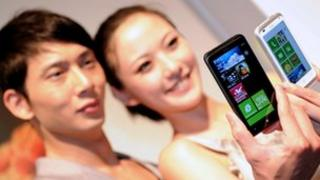 Models holding HTC phones
