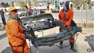 Two men carry a charred car part