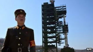 a North Korean soldier stands guard in front of an Unha-3 rocket at Tangachai-ri space centre.