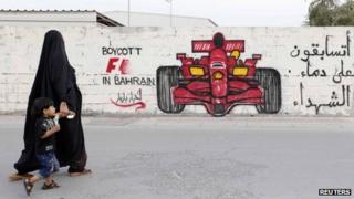 A woman and boy walk past graffiti urging the boycott of the 2012 Bahrain Grand Prix (18 April 2012)