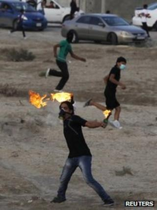 Anti-government protester throws a petrol bomb at riot police in Salambad, south of Manama (