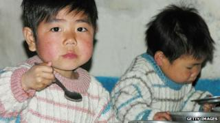 North Korean boys eat lunch in a government-run nursery