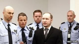 Police officers with Anders Behring Breivik in the Oslo court room where he is being tried
