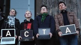 """Protesters hold up laptops spelling out """"Stop Acta"""""""