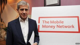 Sir Stuart Rose in front of the Mobile Money Network logo