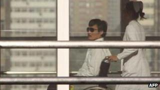 Chinese activist Chen Guangcheng (L) is seen in a wheelchair pushed by a nurse at the Chaoyang hospital in Beijing.