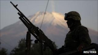 Mexican soldier on truck with machine gun in Puebla, with Popocatepetl volcano in the background