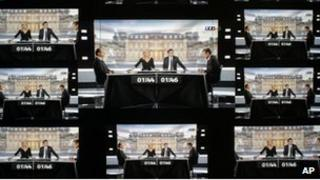 A wall screen shows the televised debate between Socialist Party candidate for the presidential election Francois Hollande and current President and conservative rival for re-election, Nicolas Sarkozy