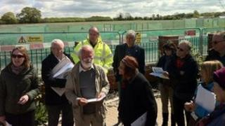 Members of the planning committee meet with the stadium site in the background